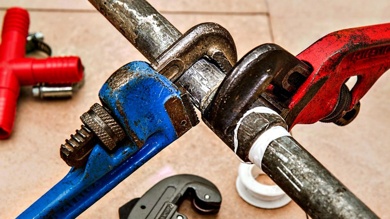 Two pipe wrenches working on a pipe and fitting